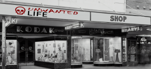 A black and white photo of a row of old shops with the sign changed to say Unwanted Life Shop